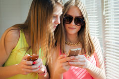 Two teenage girls looking in their gadgets Stock Photos