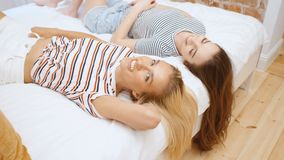 Two teenage girls lying on bed in cozy room and having fun. Two beautiful teenage girls lying on bed in cozy room and having fun stock footage