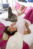 Two teenage girls (15-17) lying on bed, holding mobile phones, elevated view Stock Photo