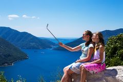 Two teenage girls in the make photo on the phone and selfie sticks on the background of Boko Kotorska bay and mountains in Montene royalty free stock images