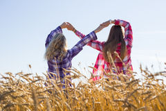 Two teenage girls making infinity sign. Two young girls plaid shirts wheat field making infinity symbol stock images