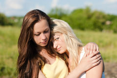 Two teenage girls, one comforts and regrets another Royalty Free Stock Image