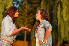 Two teenage girls. Outdoors in jeans wear talking arguing Stock Images