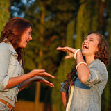 Two teenage girls. Outdoors in jeans wear talking laughing Royalty Free Stock Photography
