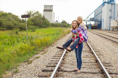 Two teenage girls piggyback railway track Stock Photography