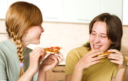 Two teenage girls with pizza Stock Photo