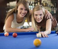 Two teenage girls playing pool Royalty Free Stock Photo