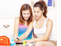Two teenage girls polishing fingernails Royalty Free Stock Photography