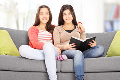 Two teenage girls posing seated on couch Stock Photo