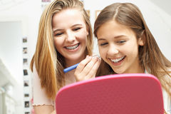 Two Teenage Girls Putting On Make Up In Bedroom Royalty Free Stock Images