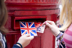 Two teenage girls putting postcards into a red letterbox Stock Image