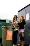 Two teenage girls recycling cds Stock Photos