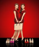 Two teenage girls in red dresses with bag Stock Image