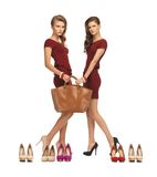 Two teenage girls in red dresses with bag Royalty Free Stock Images