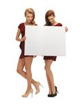 Two teenage girls in red dresses with blank board Royalty Free Stock Photography