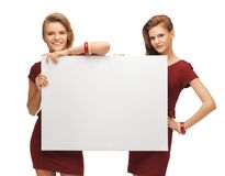 Two teenage girls in red dresses with blank board Royalty Free Stock Photo