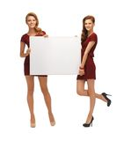 Two teenage girls in red dresses with blank board Royalty Free Stock Images