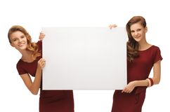 Two teenage girls in red dresses with blank board Royalty Free Stock Photos