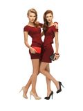 Two teenage girls in red dresses with clutches Stock Image