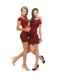 Two teenage girls in red dresses with clutches Royalty Free Stock Photo