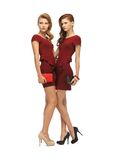 Two teenage girls in red dresses with clutches Royalty Free Stock Images