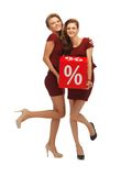 Two teenage girls in red dresses with percent sign Royalty Free Stock Photos