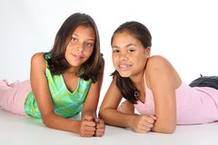 Two teenage girls relaxed lying on studio floor Royalty Free Stock Photos