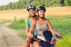 Two teenage girls riding motorcycle in the nature Royalty Free Stock Photography