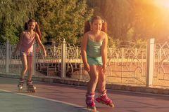 Two teenage girls, roller skates and dancing during sunset , park. stock photography