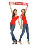 Two teenage girls with sale sign Royalty Free Stock Photography