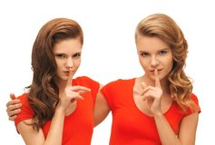 Two teenage girls showing hush gesture Royalty Free Stock Photos