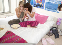 Two teenage girls (15-17) sitting on bed with popcorn, elevated view Royalty Free Stock Image
