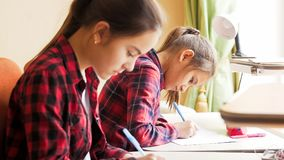 Portrait of two teenage girls sitting behind desk and writing with pens royalty free stock image