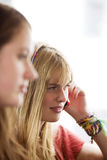 Two teenage girls sitting on a bus, one girl talking on her mobile phone Stock Photography