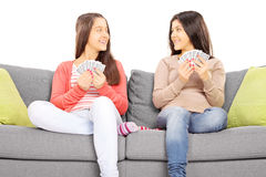 Two teenage girls sitting on couch playing cards Royalty Free Stock Photos