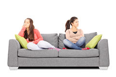 Two teenage girls sitting on sofa angry with each other Stock Image
