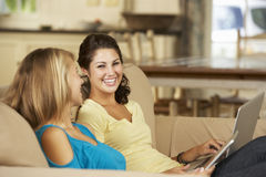 Two Teenage Girls Sitting On Sofa At Home Using Tablet Computer And Laptop Royalty Free Stock Photography