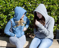 Two Teenage Girls, Sitting and Talking. Two teenage girls, white, sitting outside talking.  They are looking at each other and smiling.  Both are dressed Stock Photography