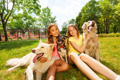 Two teenage girls sitting with three dogs in park Royalty Free Stock Images