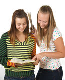 Two teenage girls smiling and reading book Royalty Free Stock Photo