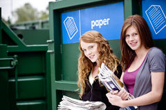 Two teenage girls standing next to a recycling container for paper Royalty Free Stock Photography