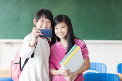 Two teenage girls student make selfie on the phone. Stock Image