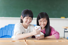 Two teenage girls student watching the phone in classroom Stock Photos