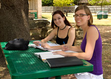 Two teenage girls studying. Two teenage girls study under an oak tree, looking at the camera and smiling Royalty Free Stock Images