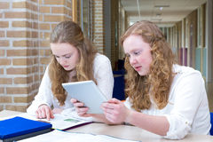 Two teenage girls studying in long school corridor. Two caucasian teenage girls studying in book and on tablet computer sitting in long school corridor Royalty Free Stock Images