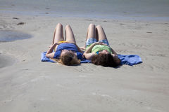 Two Teenage Girls Sunbathing at the Beach. Two teenage girls, white, sunbathing at the beach.  They are wearing colorful shorts and tank tops and are lying on Stock Image