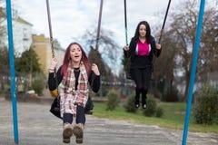 Two Teenage Girls Swinging on Swings Royalty Free Stock Photography