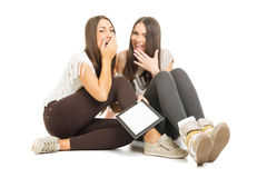 Two teenage girls with tablet having fun. Two beautiful happy Caucasian teenage girls with tablet having fun sitting on the floor isolated on white background Royalty Free Stock Photography