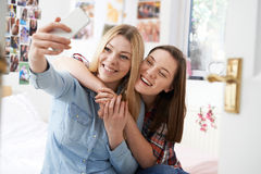Two Teenage Girls Taking Selfie In Bedroom At Home Stock Photo