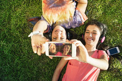 Two Teenage Girls Taking Selfie In Park Stock Photo